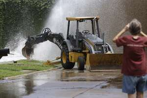 Marla Brockett takes a cell phone photo of a water main break in her neighborhood on Wembley at Lancelot Tuesday, August 30, 2016 in Houston.  Crews positioned a backhoe to limit the water from shooting up so high.  ( Melissa Phillip / Houston Chronicle )
