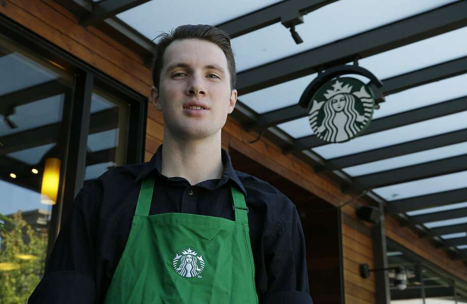 Starbucks barista Oliver Savage, 22, favors new rules, which include requiring schedule shifts two weeks in advance, and offering hours to existing employees before hiring new staff. Photo: Ted S. Warren, Associated Press