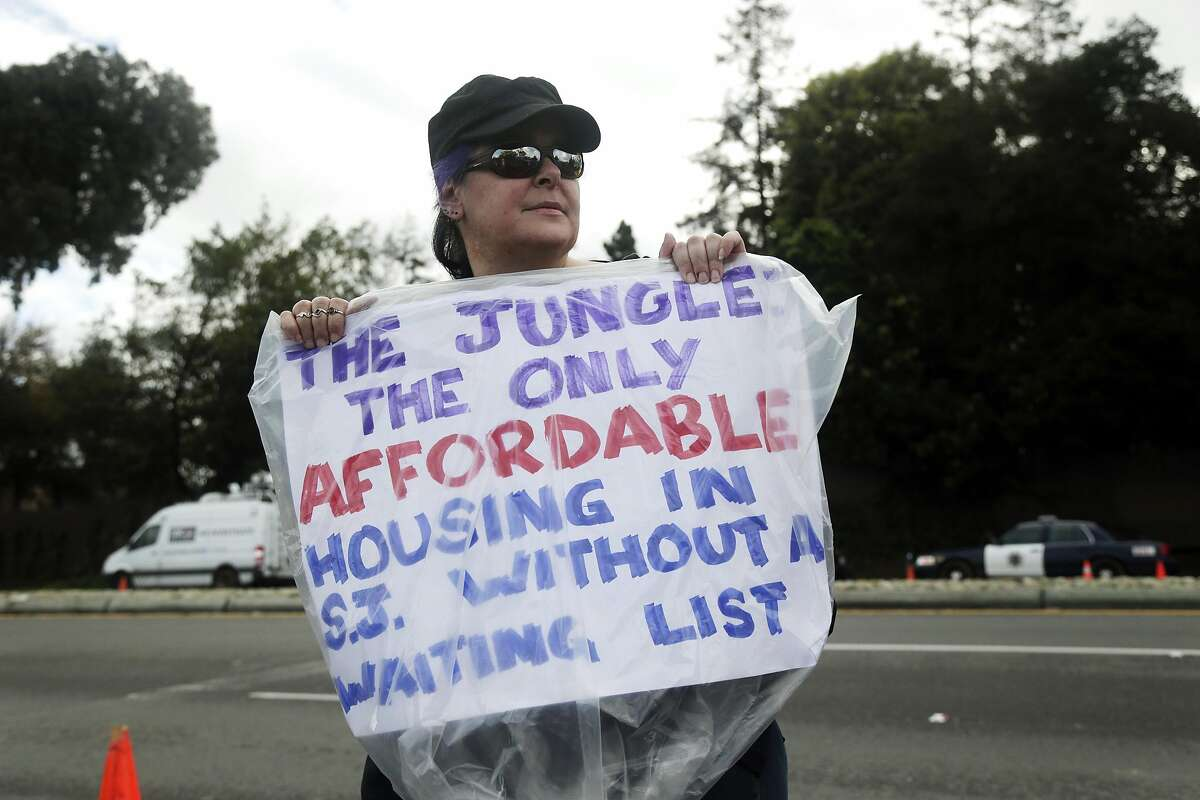 Shaunn Cartwright holds a sign in opposition of the removal of residents at a homeless encampment known as The Jungle Thursday, Dec. 4, 2014, in San Jose, Calif. Police and social-workers on Thursday began clearing away one of the nation's largest homeless encampments, a cluster of flimsy tents and plywood shelters that once housed more than 200 people in the heart of California's wealthy Silicon Valley. (AP Photo/Marcio Jose Sanchez)