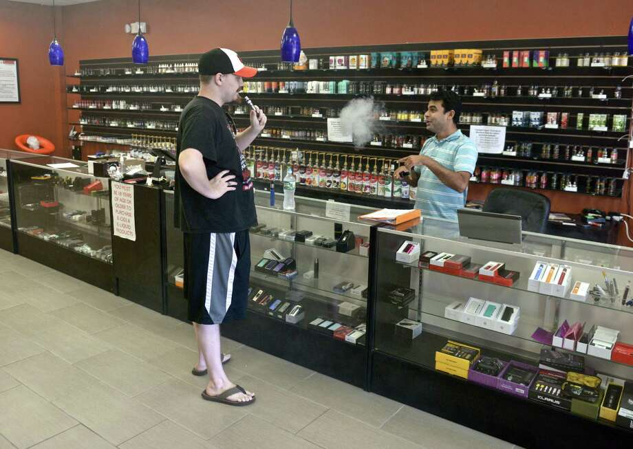 Twilight Vapor owner Saiyam Shah talks with customer Paul Clamp, of Danbury, on Tuesday. State lawmaker's are calling for new regulations on vaping. August 30, 2016, in Danbury, Conn. Photo: H John Voorhees III, Hearst Connecticut Media / The News-Times
