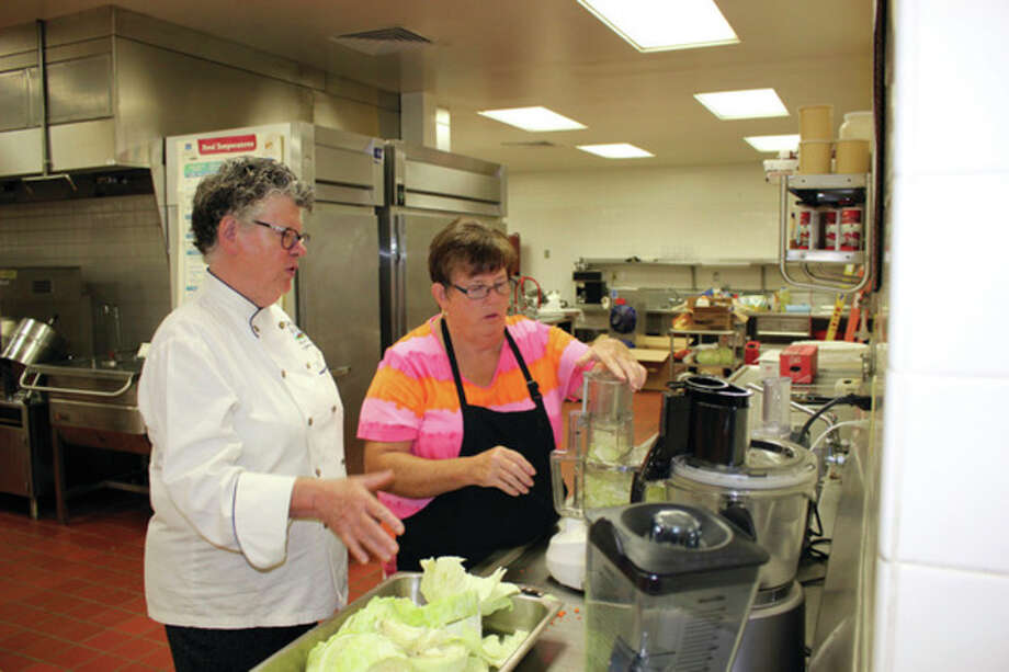 Chef Monique Hooker gives some tips as Laker food service employee Janet Paxton uses a food processor to chop cabbage for a recipe. (Submitted Photo)