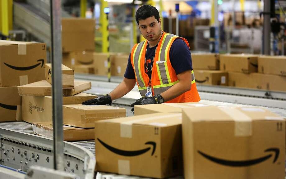 A worker at the Amazon Fullfillment Center in Schertz, TX, inspects packaging on a conveyor belt.  Thursday, April 16, 2015. Photo: Bob Owen, San Antonio Express-News