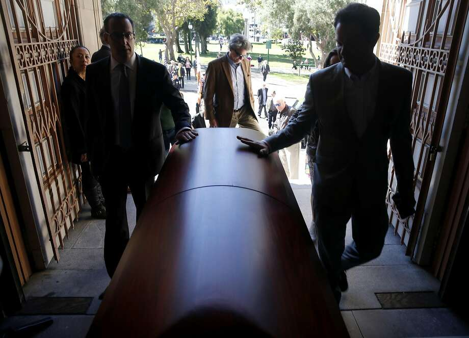 Mourners run their hands across Warren Hinckle's casket as they arrive for a funeral mass at Saints Peter and Paul Church for the longtime journalist in San Francisco, Calif. on Aug. 30, 2016. Photo: Paul Chinn, The Chronicle
