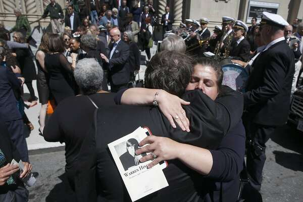 Mourners hug outside Saints Peter and Paul Church after a funeral mass was held for longtime journalist Warren Hinckle in San Francisco, Calif. on Aug. 30, 2016.