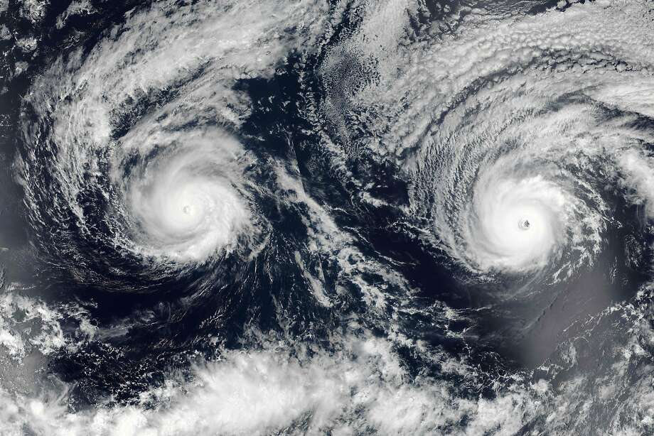 "This August 29, 2016 NASA satellite image shows Hurricanes Lester(R) (13E) and Madeline (14E) in the Pacific Ocean. The Big Island of Hawaii remains under a hurricane watch as Madeline approaches the state as a major Category 4 storm. As of late Monday, Madeline had intensified slightly with maximum sustained winds of 130 miles per hour, making it a major Category 4 hurricane. It was about 515 miles east of Hilo or 710 miles east of Honolulu, and was moving toward the west at 9 miles per hour.  / AFP PHOTO / NASA / HO / RESTRICTED TO EDITORIAL USE - MANDATORY CREDIT ""AFP PHOTO /NASA"" - NO MARKETING - NO ADVERTISING CAMPAIGNS - DISTRIBUTED AS A SERVICE TO CLIENTS  HO/AFP/Getty Images Photo: HO, AFP/Getty Images"