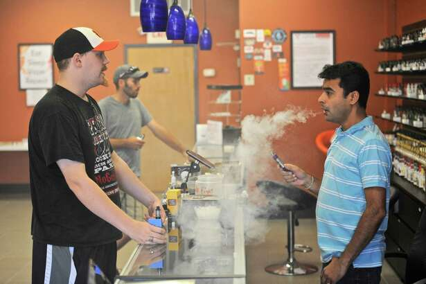 Twilight Vapor owner Saiyam Shah, right, talks with customer Paul Clamp, of Danbury, on Tuesday. State lawmaker's are calling for new regulations on vaping. August 30, 2016, in Danbury, Conn.