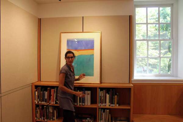 Miki Porta, of the Friends Art Committee, works to hang paintings by New Canaan resident Liana Moonie at the Curtis Gallery on Aug. 23, 2016.
