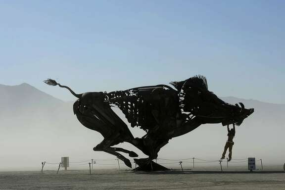 Burners play on an interactive wild boar sculpture on a dusty morning at Burning Man in the Black Rock Desert near Gerlach, Nev. on Saturday, Aug. 27, 2016. The annual festival is dedicated to community, art, self-expression and self-reliance. (Andy Barron  /The Reno Gazette-Journal via AP)