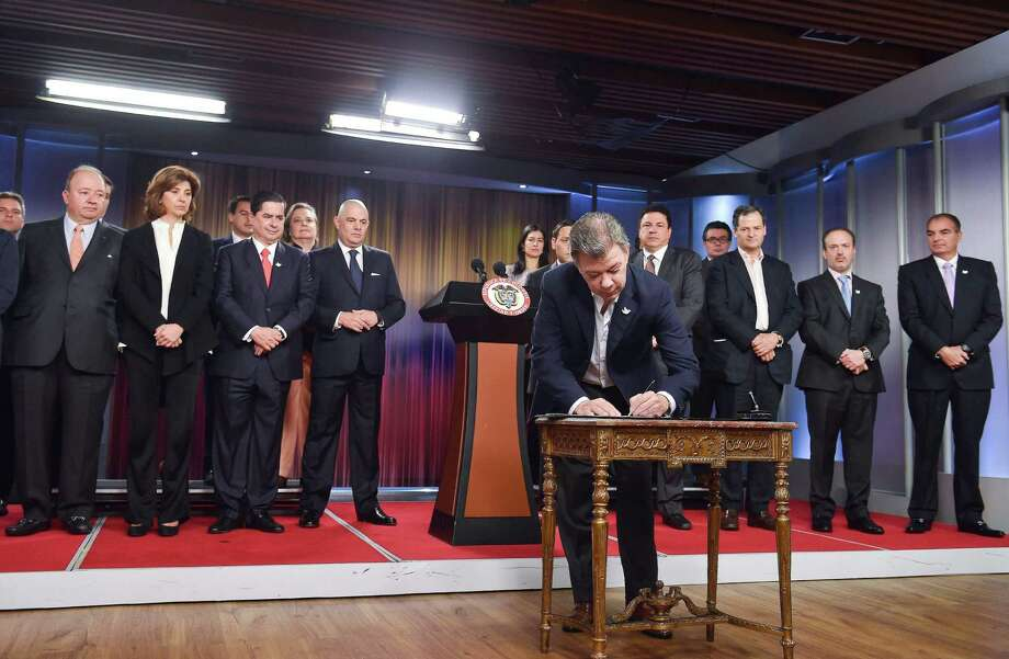 A handout picture released by the Colombian Presidency shows Colombian President Juan Manuel Santos signing a decree regarding the referendum on the government's historic peace deal with the FARC rebels, at Narino presidential palace in Bogota on August 30, 2016. (AFP / Getty Images) Photo: CESAR CARRION, Stringer / AFP or licensors