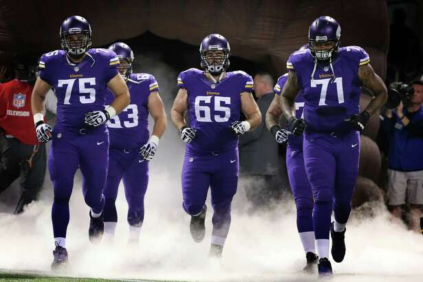 MINNEAPOLIS, MN - OCTOBER 27: John Sullivan #65, Matt Kalil #75 and Phil Loadholt #71 of the Minnesota Vikings enter the field during an NFL game against the Green Bay Packers at Mall of America Field at the Hubert H. Humphrey Metrodome on October 27, 2013 in Minneapolis, Minnesota.  (Photo by Tom Dahlin/Getty Images)