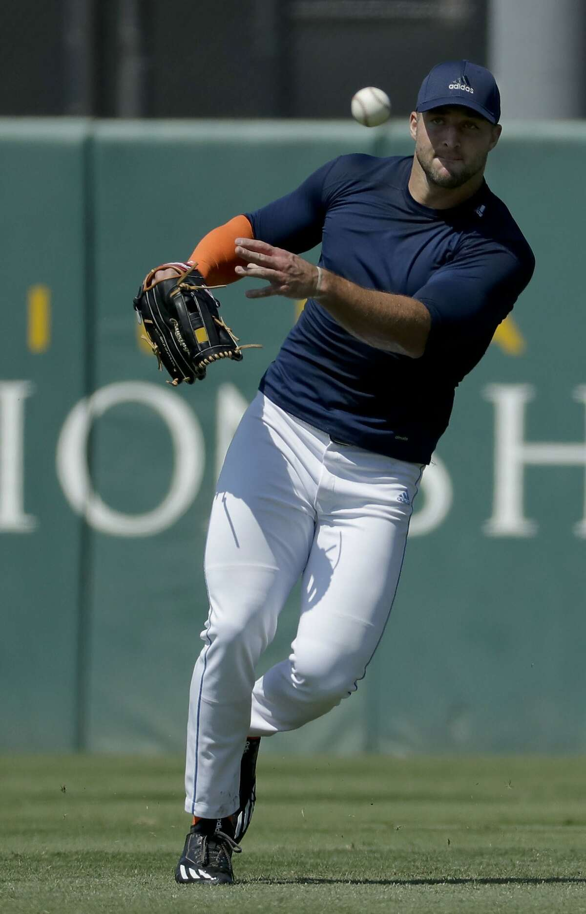 Former NFL quarterback, Tim Tebow fields a fly ball for baseball scouts and the media during a showcase on the campus of the University of Southern California, Tuesday, Aug. 30, 2016 in Los Angeles. The Heisman Trophy winner works out for a big gathering of scouts on USC's campus in an attempt to start a career in a sport he hasn't played regularly since high school. (AP Photo/Chris Carlson)