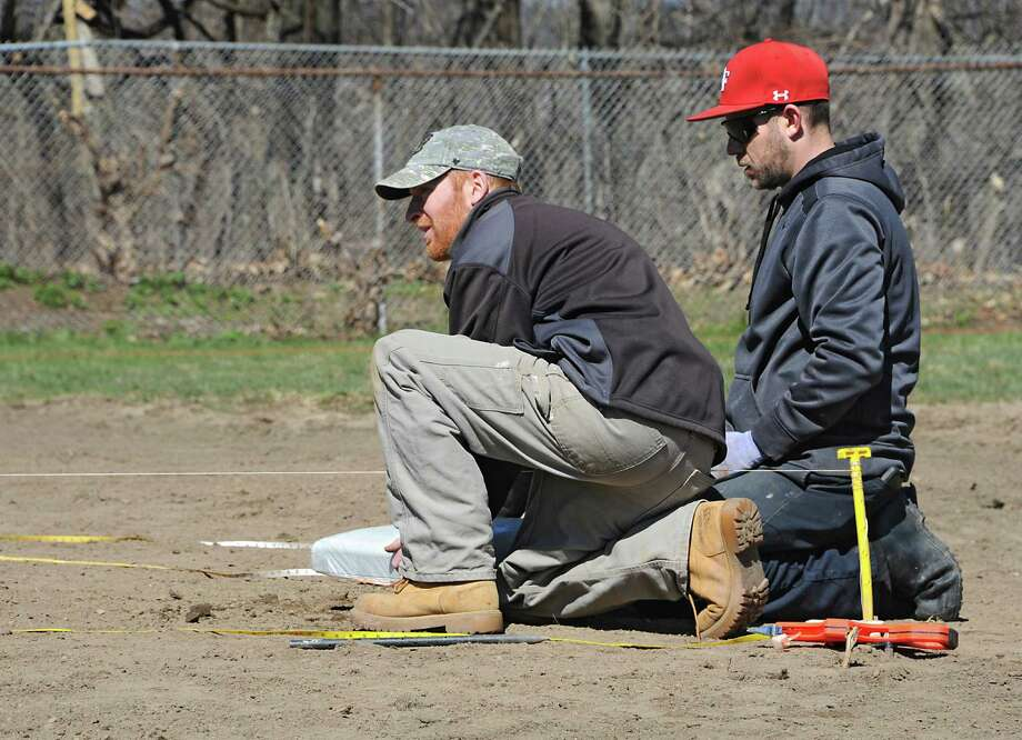 Keith Sweeney, stadium operations manager for the Tri-City ValleyCats, right, helps his General Manager Matt Callahan measure and install second base at the Upstate Premier Baseball field on Thursday, April 14, 2016 in Schenectady, N.Y. The Tri-City ValleyCats, with the support of BlueShield of Northeastern New York and Hannaford Supermarkets, renovated the Upstate Premier Baseball field on 4th Street & Campbell Avenue formerly known as Bellevue Little League. (Lori Van Buren / Times Union) Photo: Lori Van Buren / 10036166A