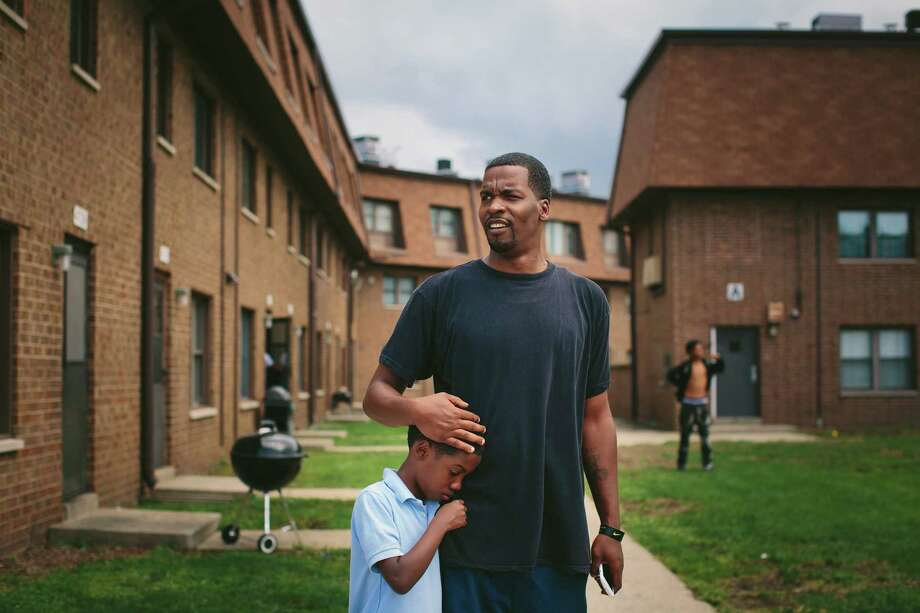 Lamont Anderson embraces his son Lamont Jr., 8, whose recent blood test revealed dangerously high levels of lead, at the West Calumet Housing Complex in East Chicago, Ind. Photo: ALYSSA SCHUKAR, STR / NYTNS