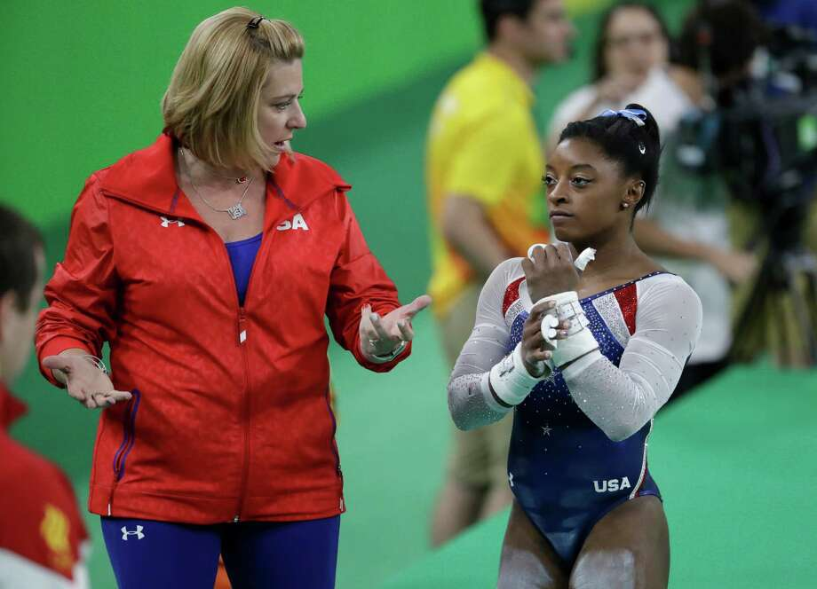Aimee Borman, left, advises Simone Biles during the all-around competition at the Olympics, one of four events in which Biles won a gold medal. Photo: Julio Cortez, STF / Copyright 2016 The Associated Press. All rights reserved. This material may not be published, broadcast, rewritten or redistribu