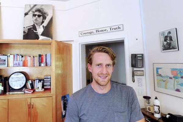 """Along with photos of musician Bob Dylan, the Brunswick School slogan """"Courage, Honor, Truth"""" can be seen in the classroom of Brunswick School English teacher James Biondi, pictured here, at the school in Greenwich. Biondi graduated from Brunswick in 2008."""
