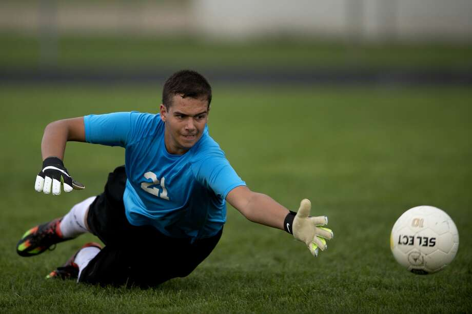 Bullock Creek goalie Clayton Nasrey stretches out to try and block a shot on goal in the second half of the Tuesday evening game. Calvary defeated Bullock Creek 4-0. Photo: Brittney Lohmiller/Midland Daily News/Brittney Lohmiller, Brittney Lohmiller/Midland Daily News