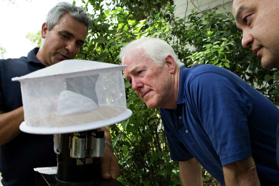 U.S. Sen. John Cornyn , center, Harris County Public Health Executive Director Dr. Umair Shah, right, and HCPH-Mosquito and Vector ControDirector Dr. Mustapha Debboun, left, take a look at trapped mosquitoes during a visit to Houston on Tuesday. Photo: Marie D. De Jesus, Staff / © 2016 Houston Chronicle