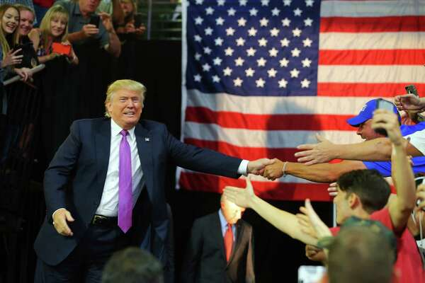 Republican Presidential candidate Donald Trump shakes hands with supporters during a rally, Tuesday, Aug. 30, 2016 at Xfinity Arena in Everett.