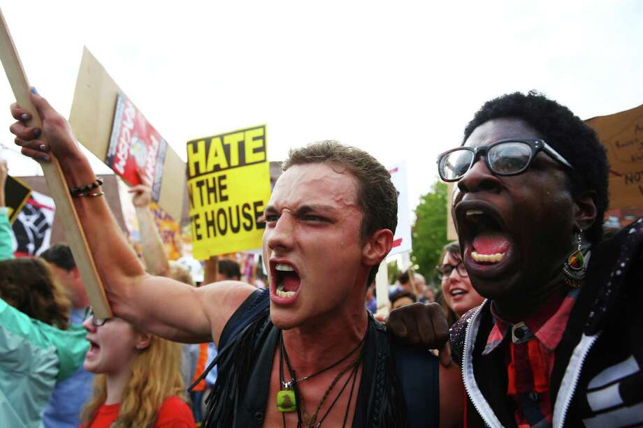 Anti-Trump protesters Gregory Vernon Enera III, left, and Krystafer Oliver at an August 2016 rally for the Republican presidential candidate in Everett.  Presidents and presidential candidates have encountered big protests, and bad happenings, for years during appearances in Western Washington.  Photo: GENNA MARTIN, SEATTLEPI.COM / SEATTLEPI.COM