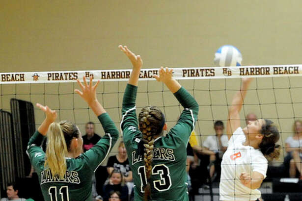 Harbor Beach's Emily Hentschl (6) attempts a kill against EPBP teammates Kaylee Krohn (13) and Kari Bushey (11).