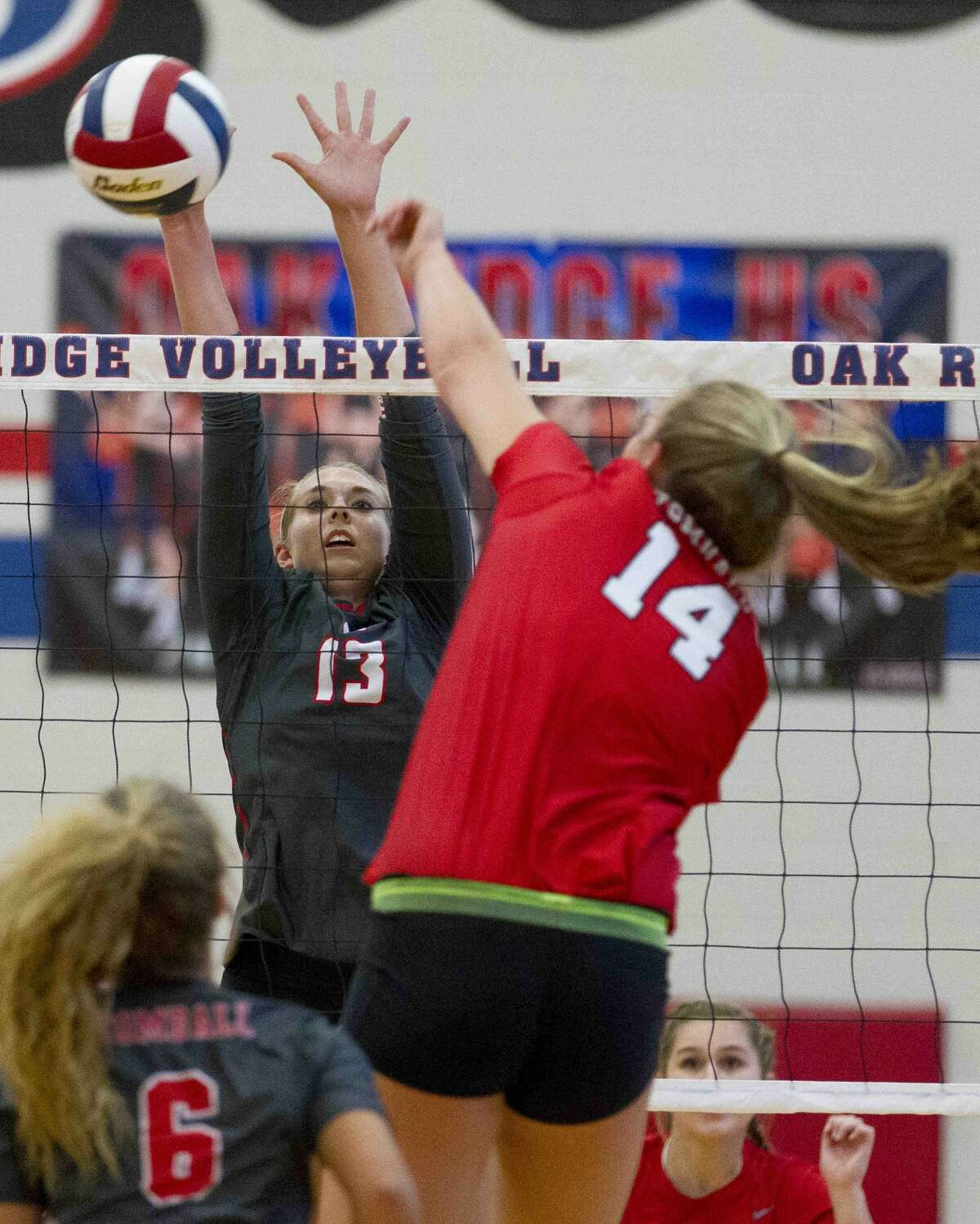 Oak Ridge middle outside hitter Brooke Clark (13) blocks a shot by Tomball right side hitter Kendall Glueck (14) during the first set of a non-district high school volleyball match Tuesday, Aug. 30, 2016, at Oak Ridge High School. Oak Ridge swept Tomball 3-0.