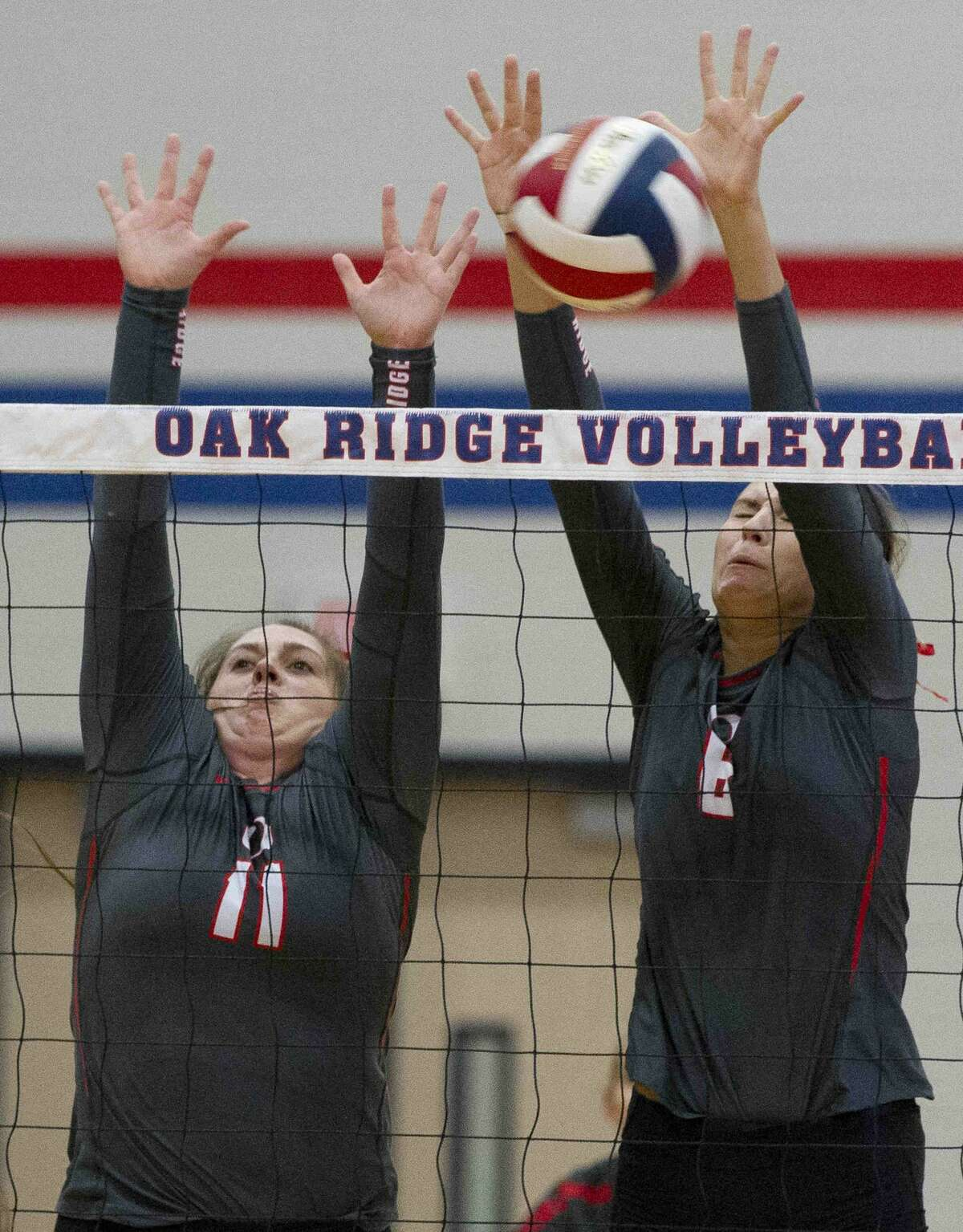 Oak Ridge setter Carly Graham (11), left, and middle blocker Molly Russell (6) block a shot by Tomball outside hitter Natalia Munoz (16) during the first set of a non-district high school volleyball match Tuesday, Aug. 30, 2016, at Oak Ridge High School. Oak Ridge swept Tomball 3-0.