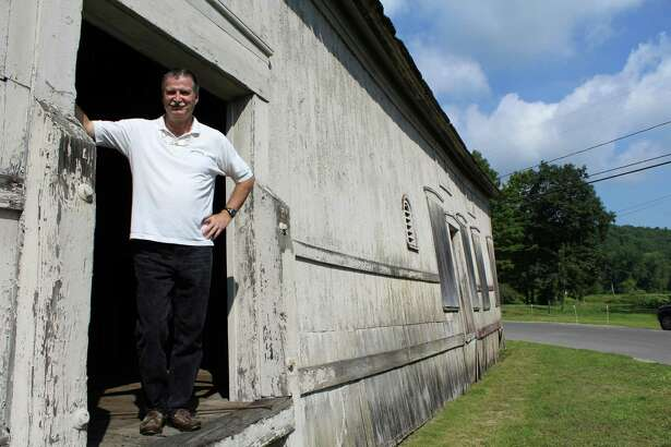 Elliott Davis, 57, in his dilapidated 1872 train station. He will soon take the station apart, and put it back together as part of his effort to create Mine Hill Distillery out of Roxbury's old transit hub.