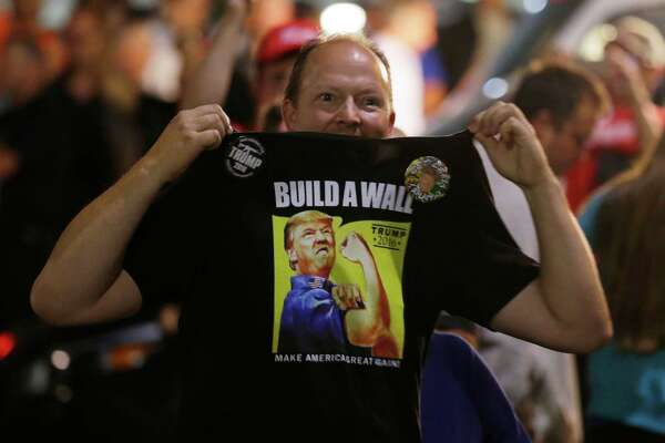 """A supporter of Republican presidential candidate Donald Trump holds up his shirt, which bears the Trump slogan """"Build a Wall,"""" following a rally for Trump, Tuesday, Aug. 30, 2016, in Everett, Wash."""