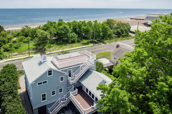 The newly renovated, lifted and expanded gray contemporary house at 228 Fairfield Beach Road offers that waterfront community lifestyle, as well as modern day amenities and a host of green features.