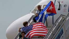 Two passengers deplane from JetBlue flight 387 waving a United States, and Cuban national flag Wednesday in Santa Clara, Cuba. JetBlue 387, the first commercial flight between the U.S. and Cuba in more than a half century, landed in the central city of Santa Clara on Wednesday morning, re-establishing regular air service severed at the height of the Cold War.