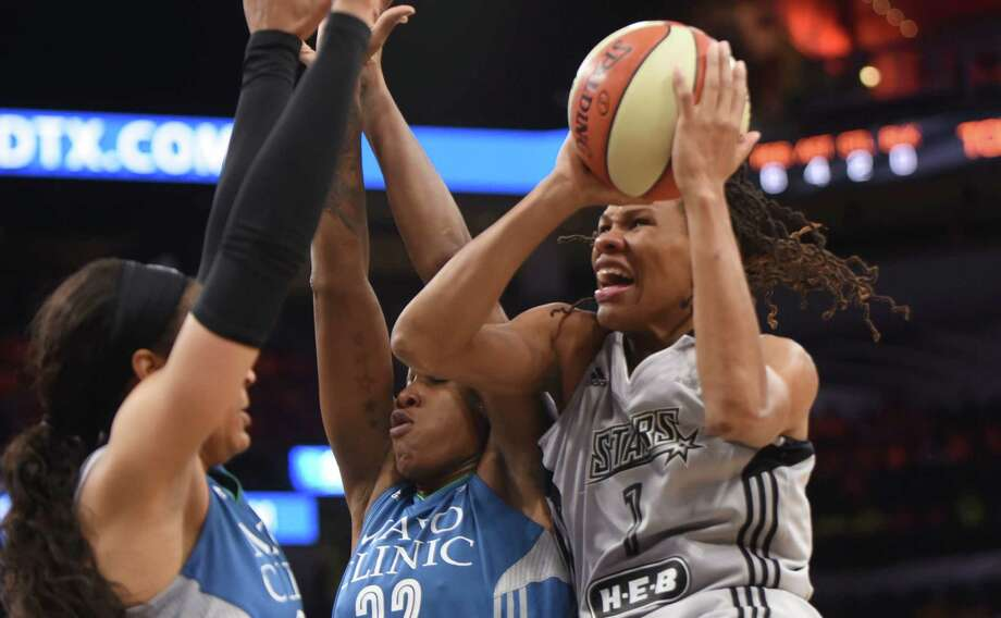 Stars' Monique Currie drives to shoot as Minnesota's Maya Moore (left) and Rebekkah Brunson defend at the AT&T Center on July 12, 2016, in San Antonio. Photo: Billy Calzada /San Antonio Express-News / San Antonio Express-News