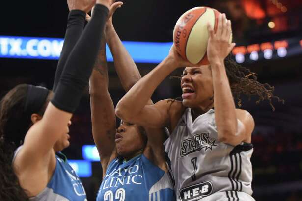 Stars' Monique Currie drives to shoot as Minnesota's Maya Moore (left) and Rebekkah Brunson defend at the AT&T Center on July 12, 2016, in San Antonio.