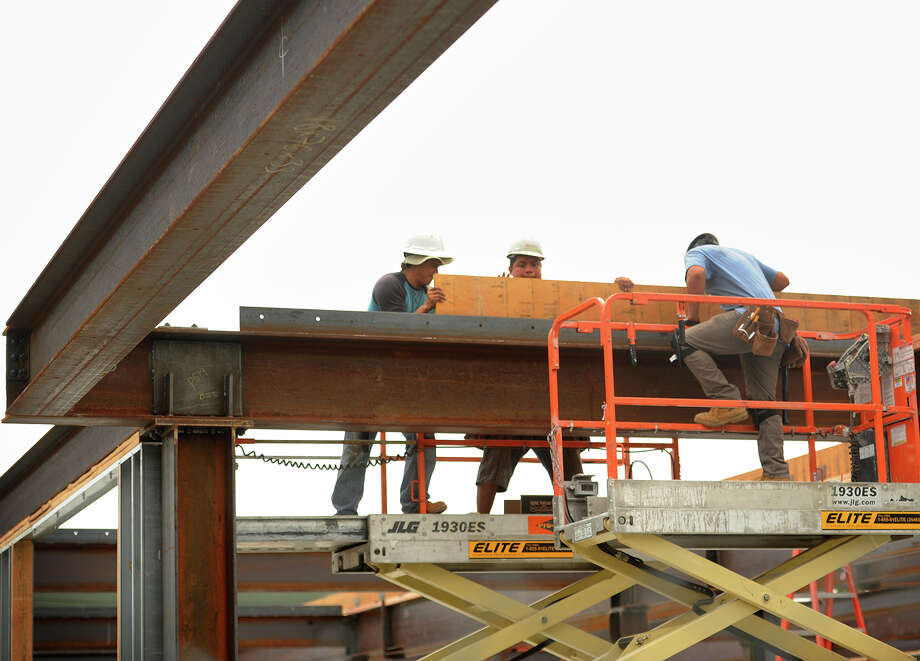 Workers attach a wooden beam to steel girders during the construction of the Bridge Street Commons luxury apartment/ retail restaurant development on Howe Avenue and Bridge Street in the heart of downtown Shelton, Conn. on Wednesday, August 31, 2016. Photo: Brian A. Pounds, Hearst Connecticut Media / Connecticut Post