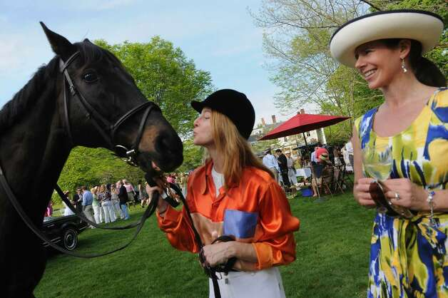 The 2nd Annual Derby Day was held at the Pequat Library in Southport, Conn. on Saturday May 01, 2010. Hundreds of locals gathered to celebrate the 136th Kentucky Derby. Here, rider Arianne Mermod goes to kiss her horse, Ben, as Erin Hornung, of Fairfield, watches during the event. After enjoying various activities on the front lawn, guests watched the race on a large TV screen inside the library. Photo: Christian Abraham / Connecticut Post