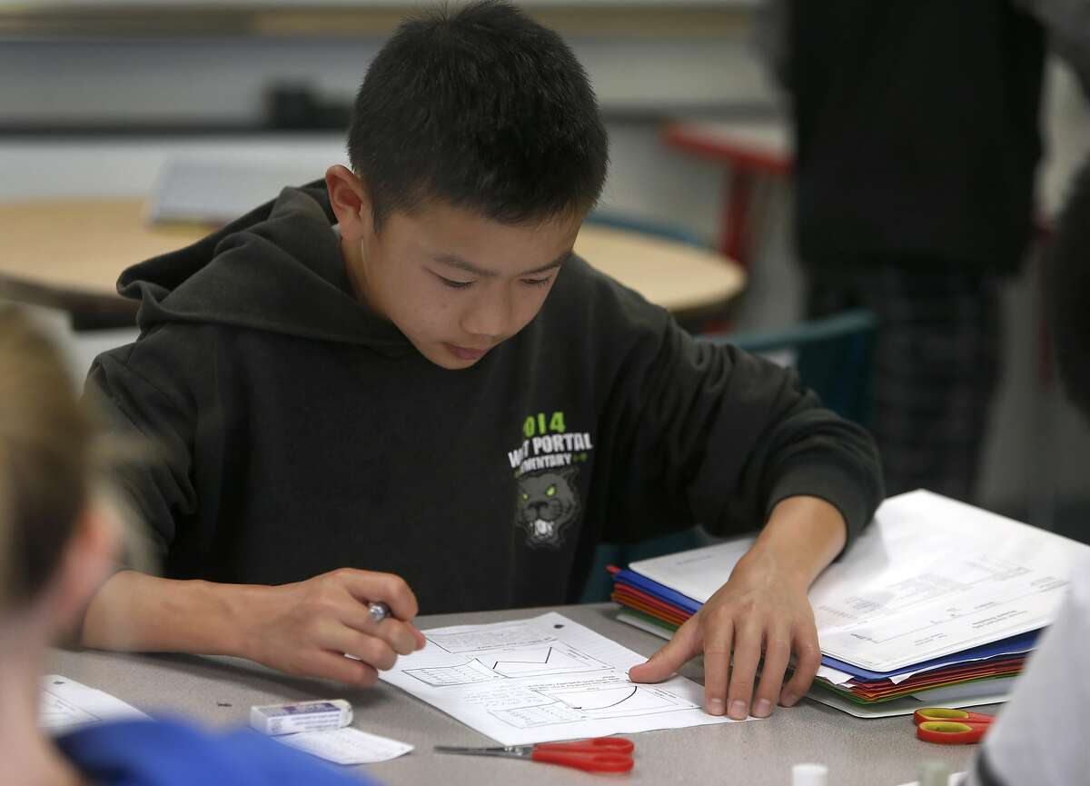 Ethan Fong solves a math problem in Sarah Kochalko's 8th grade class at Herbert Hoover Middle School in San Francisco, Calif. on Aug. 31, 2016. Salesforce CEO and philanthropist Marc Benioff is announcing another year of grants to help fund San Francisco schools.