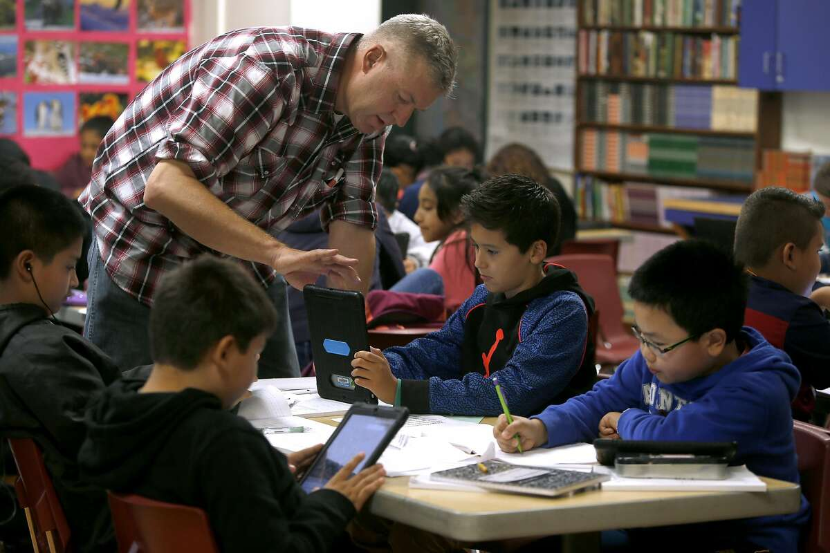 Teacher Nathan Steller helps a student with his classroom-issued iPad, which was funded with a grant from Marc Benioff, at Herbert Hoover Middle School in San Francisco, Calif. on Aug. 31, 2016. Salesforce CEO and philanthropist Marc Benioff is announcing another year of grants to help fund San Francisco schools.