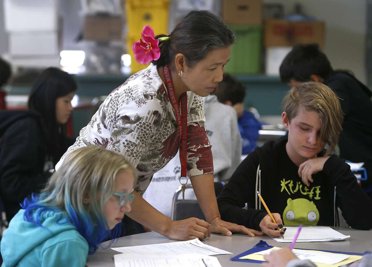 Teacher Chanmony Prak helps her 6th grade students with a math problem at Herbert Hoover Middle School in San Francisco, Calif. on Aug. 31, 2016.