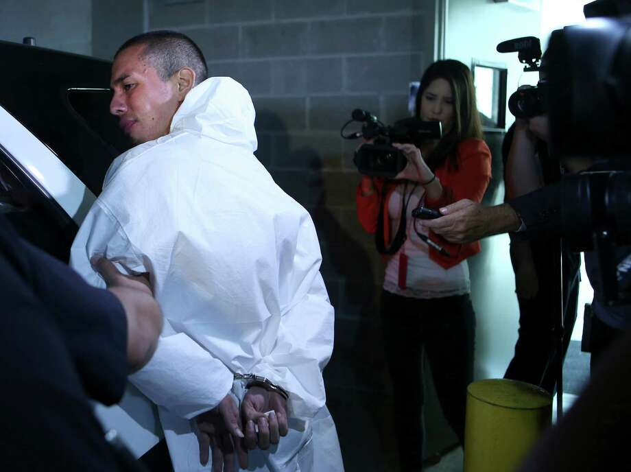 Ralph Torres is escorted out of police headquarters Wednesday, Aug. 31, 2016 on his way to jail. Police say Torres will be charged will capital murder for allegedly killing a convenience store clerk. SAPD also say he is a suspect in the shooting of two other people and at least 5 robberies, crimes he could be charged with later. Photo: William Luther, San Antonio Express-News / © 2016 San Antonio Express-News