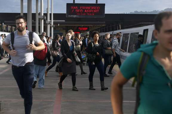 Passengers cross the platform to transfer to a San Francisco-bound train at the MacArthur BART station in Oakland, Calif. on Aug. 30, 2016.