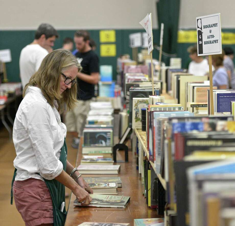 File photo from last year's fair. Sarah Upson, a volunteer at the Mark Twain Library 55th Annual Book Fair, straightens up a table of books at the fair, held at the Redding Community Center, on September 5, 2015, in Redding, Conn. Photo: H John Voorhees III / Hearst Connecticut Media / The News-Times