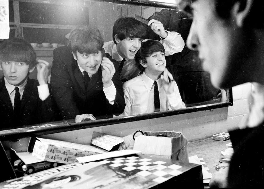 Above: George Harrison (left), John Lennon, Paul McCartney and Ringo Starr check their hair before a show. Right: McCartney and Lennon with radio reporter Larry Kane (center), who offers his memories in the film. Photo: Apple Corps Ltd.