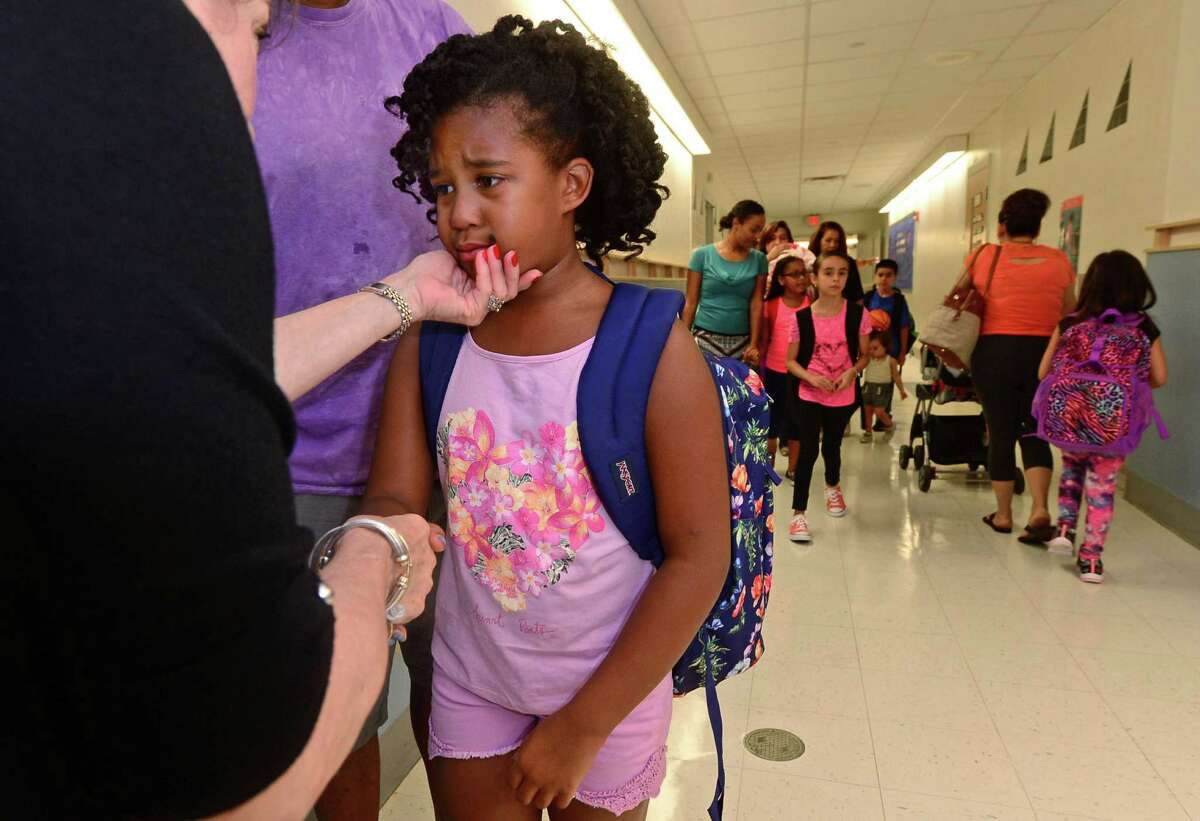 Tahlia Zoe, is comforted by her second-grade teacher Linda Walker during their first day of class at Brookside Elementary School Wednesday in Norwalk.
