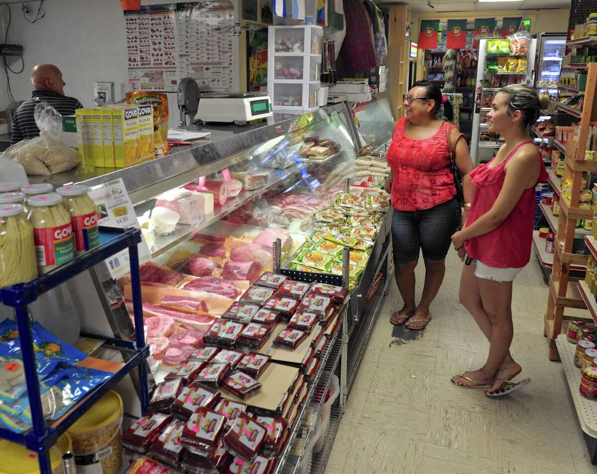 Iuany Nascemento, center, and Luana Albuquerque, right, shop for some meat through José Belizeário at Fernandes Food Store. Stores like the Fernandes Food Store which carry a variety of fresh produce and meat, will not be affected by the new USDA regulation that would require stores that except food stamps to stock fruits and vegetables. Wednesday, August 31, 2016, in Danbury, Conn.