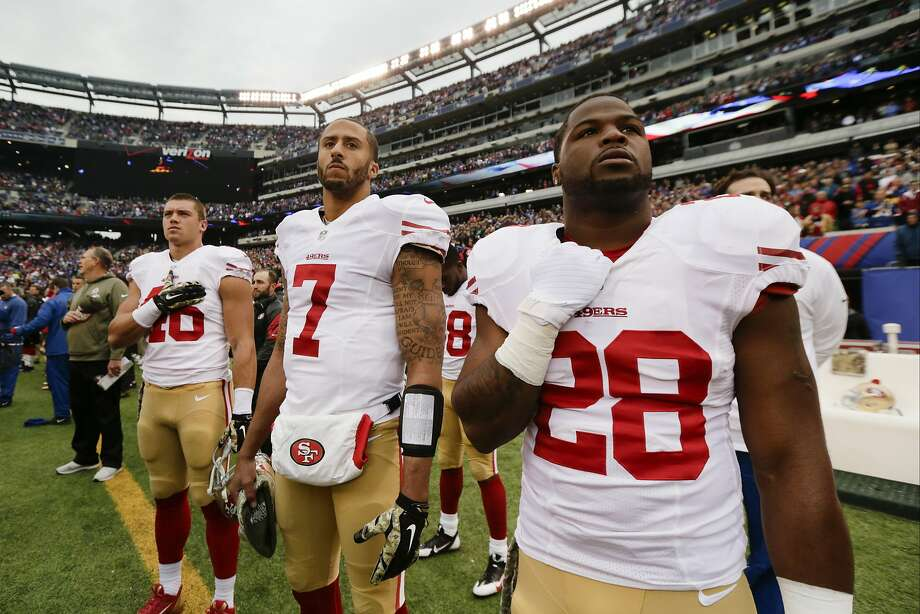 San Francisco 49ers quarterback Colin Kaepernick (7) stands with teammates Derek Carrier (46) and Carlos Hyde (28) during the playing of the national anthem before an NFL football game against the New York Giants Sunday, Nov. 16, 2014, in East Rutherford, N.J.  (AP Photo/Julio Cortez) Photo: Julio Cortez, AP