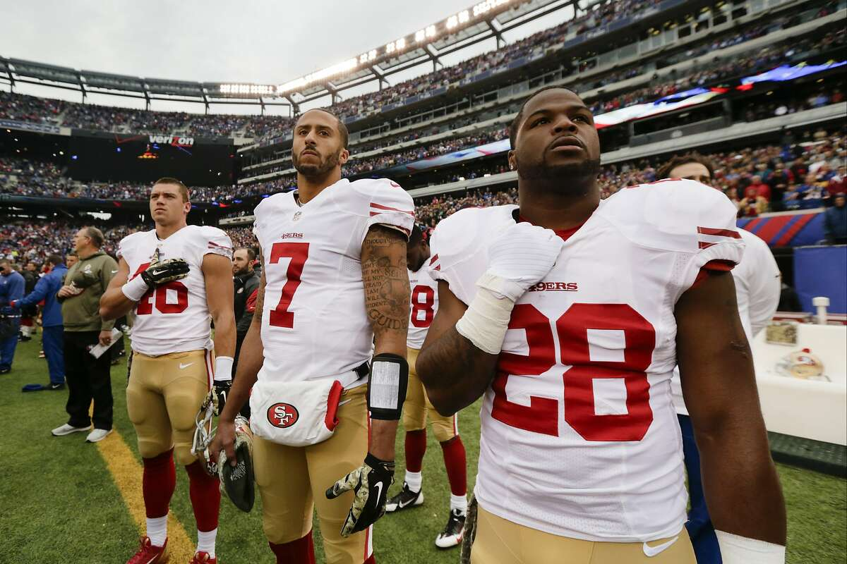 San Francisco 49ers quarterback Colin Kaepernick (7) stands with teammates Derek Carrier (46) and Carlos Hyde (28) during the playing of the national anthem before an NFL football game against the New York Giants Sunday, Nov. 16, 2014, in East Rutherford, N.J. (AP Photo/Julio Cortez)
