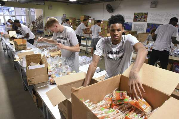 """Dejounte Murray of the Spurs helps bag and pack food products for the San Antonio Food Bank """"BackPack"""" program on Aug. 31, 2016."""
