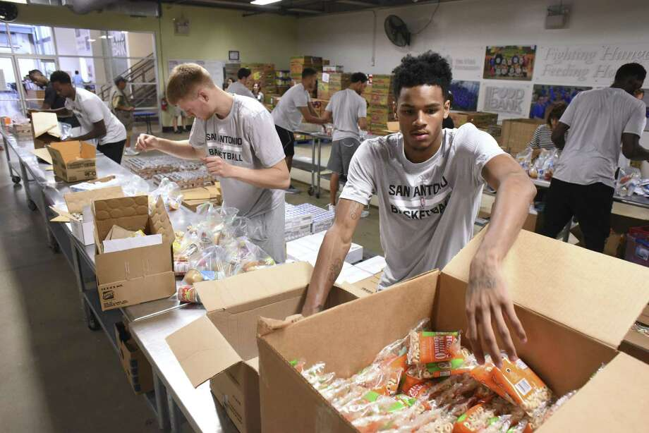 There has long been recognition that home needs can affect students' learning, why food drives such as these have been crucial. Dejounte Murray of the San Antonio Spurs helps bag and pack food products for the San Antonio Food Bank BackPack Program in August. Now, however, schools are taking it on themselves to keep food pantries and clothes closets. Churchill High School, for instance, has a food pantry. Photo: Billy Calzada /San Antonio Express-News / San Antonio Express-News