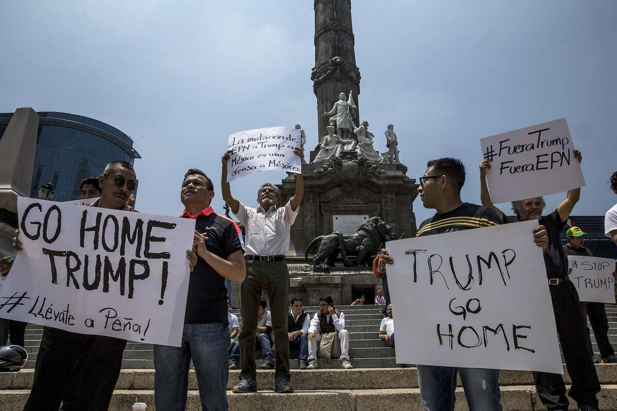 Demonstrators holds signs at the Angel of Independence monument in downtown Mexico City as Donald Trump traveled there, Aug. 31, 2016. President Enrique Pena Nieto is being criticized by many Mexicans for his willingness to meet with Trump, the Republican presidential candidate who has made hostility to immigration a central plank of his campaign. (Adriana Zehbrauskas/The New York Times)