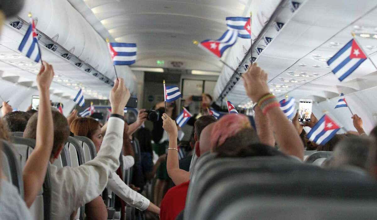 Shortly after take-off from Fort Lauderdale, customers wave Cuban flags while onboard JetBlue's inaugural commercial flight to Cuba on Wednesday. (Donald Traill/AP Images for JetBlue)