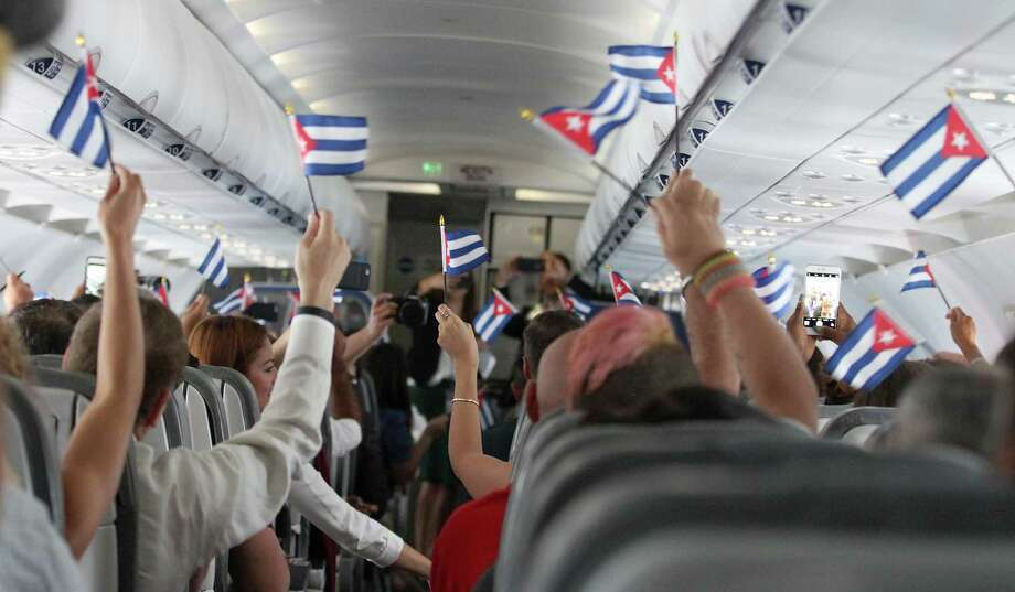 Shortly after take-off from Fort Lauderdale, customers wave Cuban flags while onboard JetBlue's inaugural commercial flight to Cuba on Wednesday. (Donald Traill/AP Images for JetBlue) Photo: Donald Traill, Associated Press / AP Images